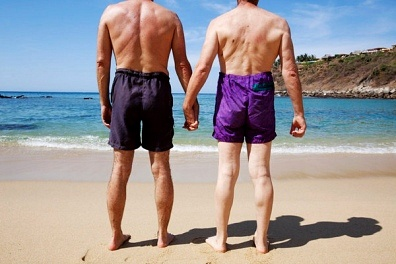 two men holding hands on a beach
